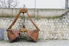 Old orange and rusty Crane bucket in front of a wall. stock images