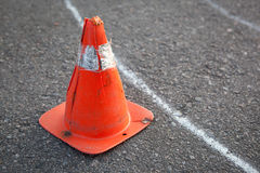 Old orange striped cone on road. Royalty Free Stock Images