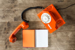 Old orange telephone and blank notebook Royalty Free Stock Image