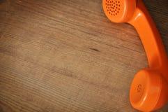 Old orange telephone receiver Royalty Free Stock Photos
