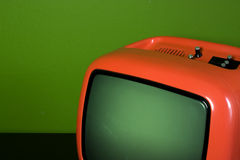 Old orange television in green room. Detail of old orange television in green room Royalty Free Stock Images