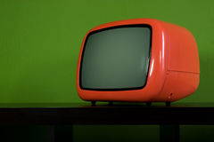 Old orange television in green room. Detail of old orange television in green room Stock Photography