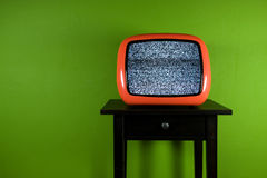 Old orange television with interruption. In green room Royalty Free Stock Photography