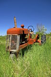 Old orange tractor. Old one wheeled orange tractor parked in the long grass Stock Photo