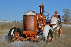 An old orange tractor sits in the snow. An old orange tractor is parked in the weeds partially covered with snow Royalty Free Stock Image