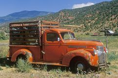 An old, orange truck rests abandoned in a Colorado field, Snowmass, Colorado Royalty Free Stock Images