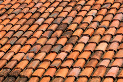 Old orange weathered roof shingles. Dirty stained ceramic tiles Royalty Free Stock Images