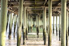 Old Orchard Beach Pier Supports. The structural supports underneath old orchard beach pier as the waves flow around them royalty free stock image