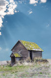 Old Oregon Homestead. Vertical image of a derelict Eastern Oregon Homestead with sun rays shining through the clouds Royalty Free Stock Images