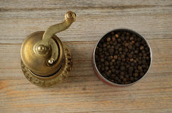 Old oriental pepper mill and black pepper peas Royalty Free Stock Image