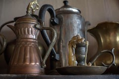 Old oriental teapots and candlestick. On a background of gray wall Royalty Free Stock Images