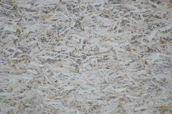 An old oriented strand board OSB , fiberboard background of texture. Sheet is made of brown wood chips pressed together into a woo. Den floor royalty free stock images