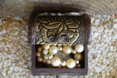 Old ornamental jewelry box and a white pearl necklace, a suitcase with a treasure from above Stock Photography