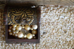 Old ornamental jewelry box and a white pearl necklace, a suitcase with a treasure, from above on the left side stock images