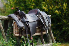 Old ornamental saddle on the wooden fence. At summer time Stock Photos