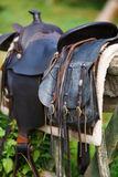 Old ornamental saddle on the wooden fence Stock Photography