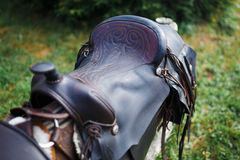 Old ornamental saddle on the wooden fence. At summer time Royalty Free Stock Image