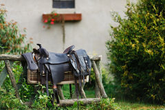 Old ornamental saddle on the wooden fence Royalty Free Stock Photo