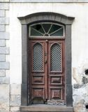 Old ornate brown double house door with broken repaired panels and hand shaped knocker with stone frame and doorstep. An old ornate brown double house door with royalty free stock image