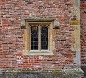 Old ornate concrete window with stained glass in a weathered brick wall in an old manor house royalty free stock photo