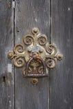 Old ornate rusty door knocker. Old  ornate rusty door knocker on wooden door Royalty Free Stock Photo