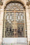 Old Ornate Scrollwork on Door. An old rusty metal door of glass and scroll work Stock Photo