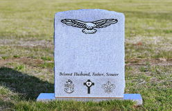Old tombstone with engraved eagle, USN, scouts,. Old granite gravestone with engraved eagle, USN, Cross, Boy Scouts royalty free stock image