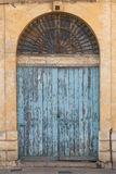 Old ornate wooden doorway painted blue. Traditional Maltese ancient blue wooden doorway with flaking paint, shot straight-on in Valletta, Malta, Europe Royalty Free Stock Photos