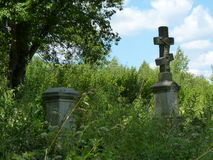 Old Orthodox cemetery with tombstones and stone cross. Royalty Free Stock Photos