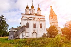 Old orthodox church at village. Summer view with floral meadow. Sun flare. Old orthodox church at village. Summer view with floral meadow. Sunny day, blue sky stock images