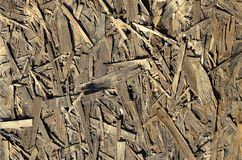 Old OSB boards are made of brown wood chips sanded into a wooden background. Top view of OSB wood veneer chipboard background, ti. Ght, seamless surfaces Royalty Free Stock Photography