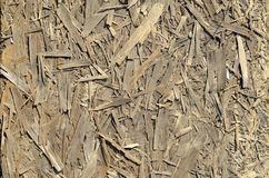 Old OSB boards are made of brown wood chips sanded into a wooden background. Top view of OSB wood veneer chipboard background, ti. Ght, seamless surfaces Royalty Free Stock Photos