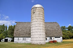 Old outdated silo and barn once used for a dairy operation Stock Photos