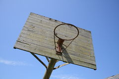 Old outdoor basketball hoop against blue sky Stock Photo
