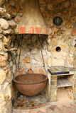 Old Outdoor Kitchen. Old fashioned outdoor, rustic pioneer kitchen made of stone with iron and copper pots Royalty Free Stock Photos