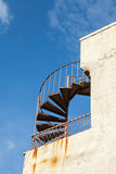 Old outdoor metal spiral ladder on the wall. Abstract architecture fragment, old outdoor metal spiral ladder on the wall Royalty Free Stock Photos