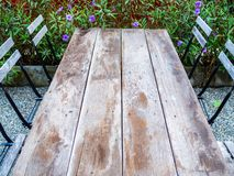 Old outdoor wooden dining table on gravel floor. Old outdoor wooden dining table and wooden chairs on gravel floor on garden background. Wooden table top royalty free stock images