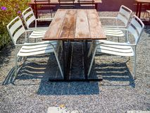 Old outdoor wooden dining table on gravel floor. Old outdoor wooden dining table and four white steel armchairs on gravel floor royalty free stock photography