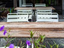 Old outdoor wooden dining table on gravel floor. Old outdoor wooden dining table and white steel chairs on gravel floor royalty free stock photo