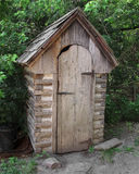 Old outhouse in the trees. Royalty Free Stock Photography