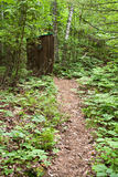 Old Outhouse in the Woods. An old outhouse on the trail through the woods royalty free stock images