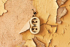 Old  outlet and cable on a decrepit wall Stock Image