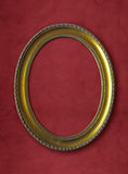 Old oval golden frame on red wall Royalty Free Stock Photo