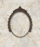 Old oval picture frame metal worked on marble background Royalty Free Stock Images