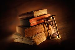 Old overlapping books with ancient hourglass stock image