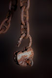 Old padlock. A slightly isolated photo of an old rusty padlock hanging on anchor chain on a very blurry background Royalty Free Stock Photo