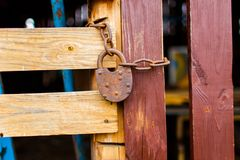 Old padlock attached to the wooden wall of shed with metal chain stock photo