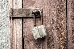 Old padlock. On a background of a wooden door Stock Images