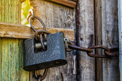 Old padlock. With chain on wooden gate Royalty Free Stock Image