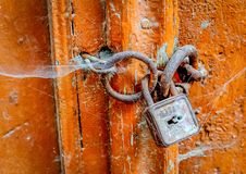 Old padlock. Old fashioned padlock, orange door and spider net Royalty Free Stock Photos